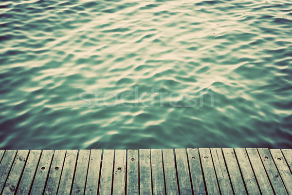 Grunge wood boards of a pier over ocean with rippling waves. Vintage Stock photo © photocreo