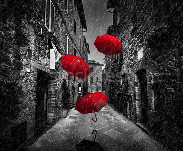 Umrbellas flying with wind and rain on dark street in an old Italian town in Tuscany, Italy Stock photo © photocreo