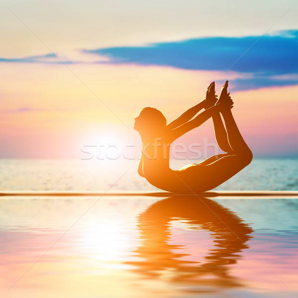 A silhouette of a woman in bow yoga position, meditating against sunset sky Stock photo © photocreo