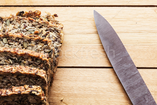 Stock photo: Knife and wholemeal, wholewheat bread on wooden table. Organic, healthy food
