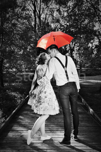 Young romantic couple in love flirting in rain. Red umbrella Stock photo © photocreo
