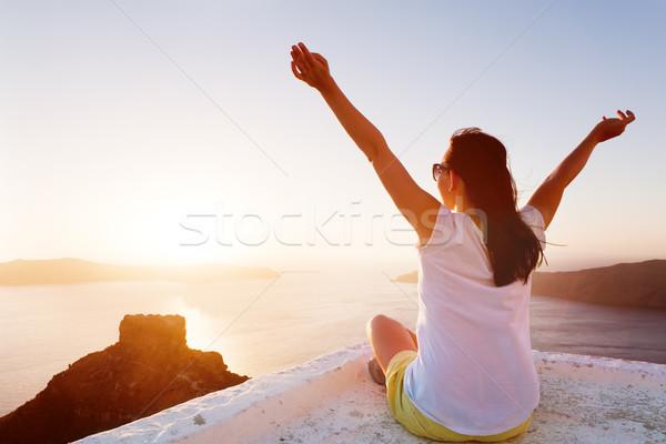 Fiatal nő kezek magasban kilátás Santorini Görögország naplemente Stock fotó © photocreo