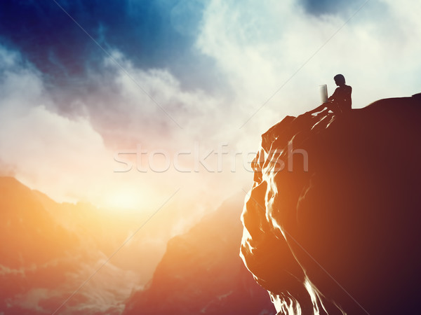 A man working on laptop sitting on the peak of a mountain at sunset. Stock photo © photocreo