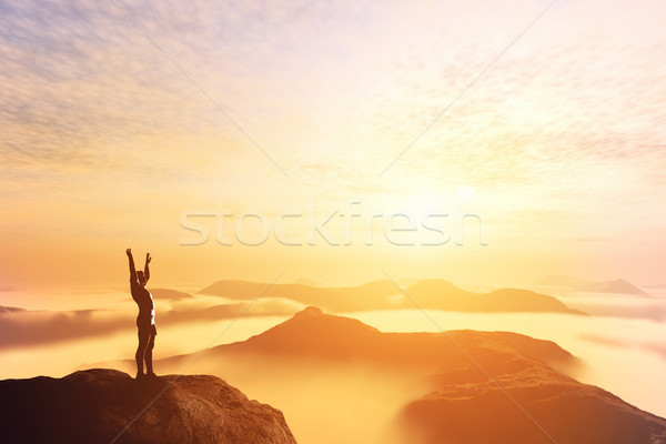 Happy man with hands up on the top of the world above clouds. Bright future Stock photo © photocreo