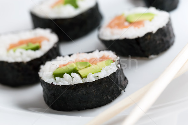 Stock photo: Sushi rolls with salmon, avocado, rice in seaweed and chopsticks on a plate.