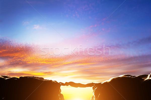 Man serving as a bridge over precipice between two mountains Stock photo © photocreo