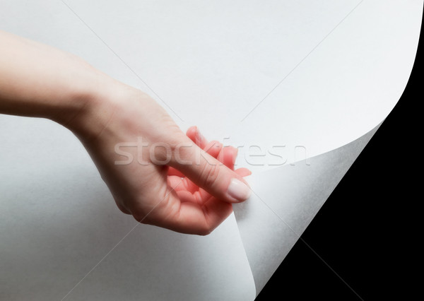 Hand pulling a paper corner to uncover, reveal something Stock photo © photocreo