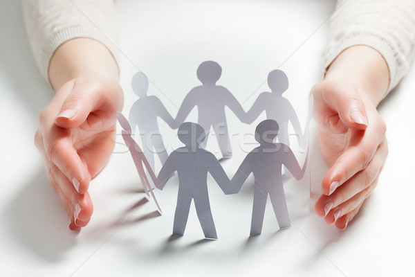 Paper people surrounded by hands in gesture of protection. Concept of insurance Stock photo © photocreo