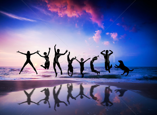 People and dog jumping on the beach. Happiness Stock photo © photocreo