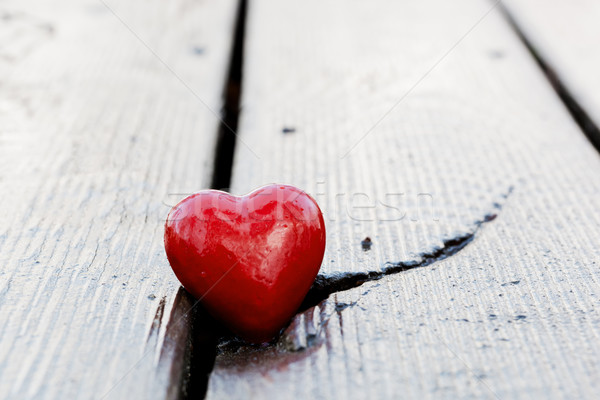 Red heart in crack of wooden plank. Symbol of love Stock photo © photocreo