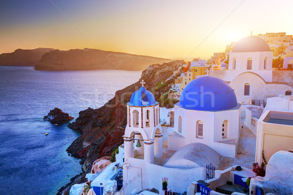 Oia town on Santorini island, Greece at sunset. Rocks on Aegean sea. Stock photo © photocreo