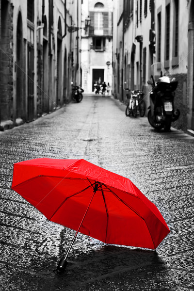 Red umbrella on cobblestone street in the old town. Wind and rain Stock photo © photocreo