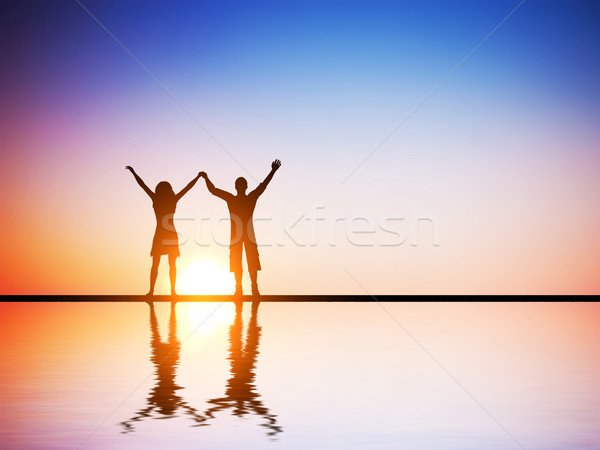 A happy couple in love standing together with hands raised at sunset Stock photo © photocreo