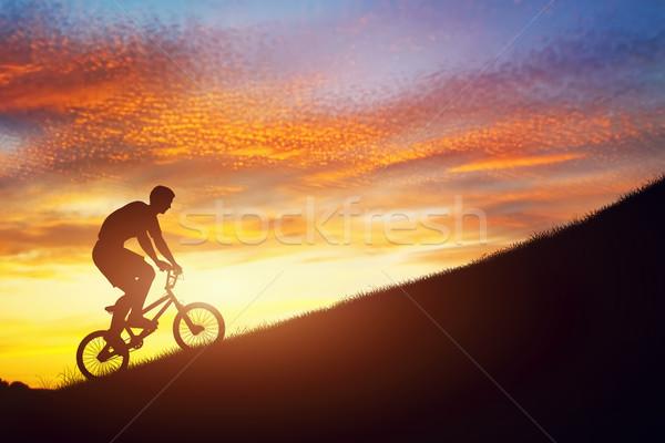 Man riding a bmx bike uphill against sunset sky. Strength, challenge. Stock photo © photocreo