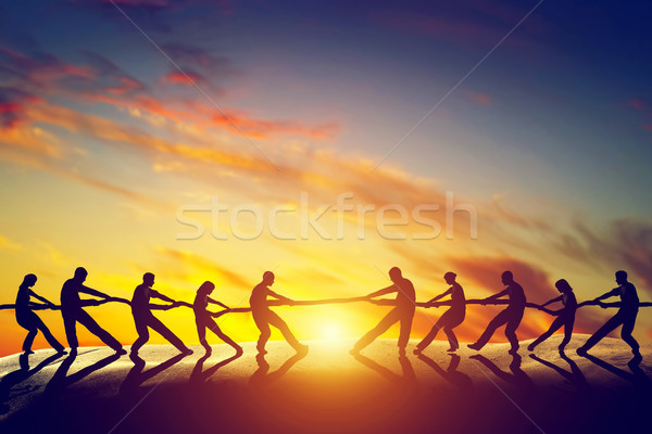 Two groups of people pulling line, playing tug of war. Stock photo © photocreo