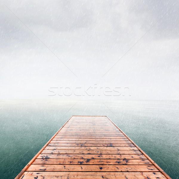 Wooden jetty, pier on deep cold sea, ocean. Raining sky Stock photo © photocreo