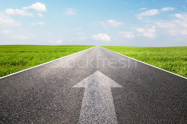 Arrow sign pointing forward on long empty straight road, highway Stock photo © photocreo