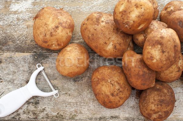 Pile of farm fresh potatoes with dirt and peeler Stock photo © photohome