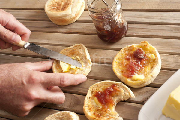 Man spreading crumpets with jam and butter Stock photo © photohome