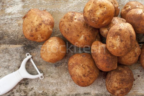 Pile of round baking potatoes beside peeler Stock photo © photohome