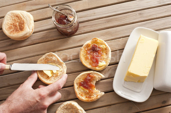 Man buttering a fresh crumpet for breakfast Stock photo © photohome