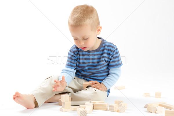 Mały cute chłopca gry budynków wielokondygnacyjnych odizolowany Zdjęcia stock © Photoline