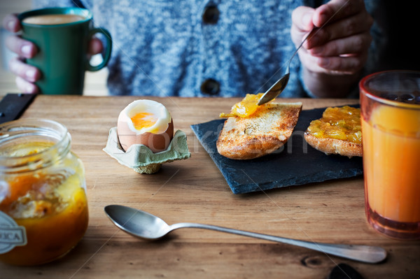 Breakfast with soft boiled egg, orange juice, toast with jam and coffee with milk. Stock photo © Photooiasson