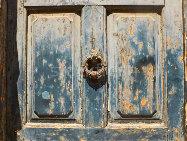 Antique blue door with a rusty metal ring knob background. Stock photo © Photooiasson