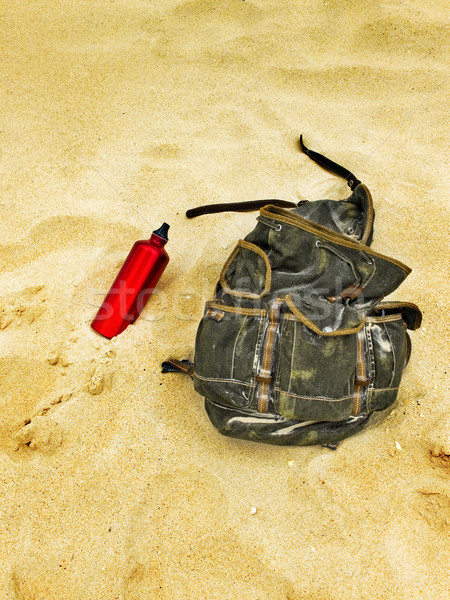 Backpack and canteen water bottle in the sand of a beach. Stock photo © Photooiasson