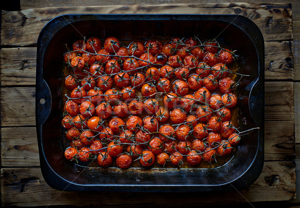 Ripe Cherry tomatoes branches roasted in a metallic oven dish. Stock photo © Photooiasson