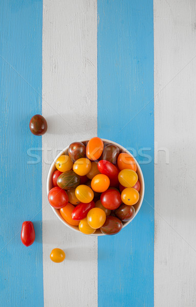A bowl with multicolored fresh ecologic tomatoes. Stock photo © Photooiasson