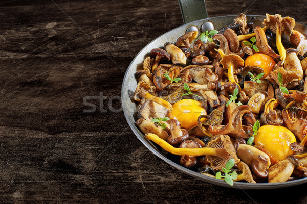 Frying pan steel with mushrooms and soft egg yolks. Stock photo © Photooiasson