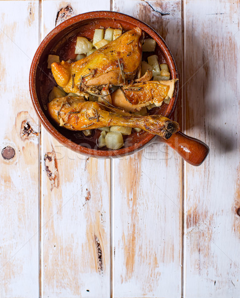 Grilled chicken with potatoes in a rustic bowl. Typical spanish tapa. Stock photo © Photooiasson