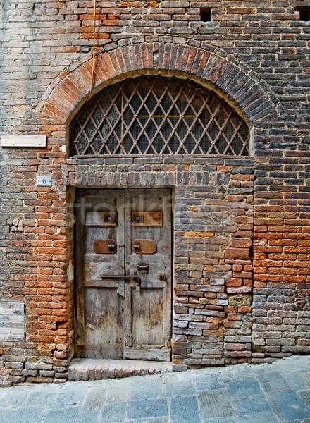 Antiqu door in Siena street. Siena, Italy Stock photo © Photooiasson
