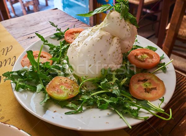 Burrata of Puglia seasoned and piled with wild rocket salad. Stock photo © Photooiasson