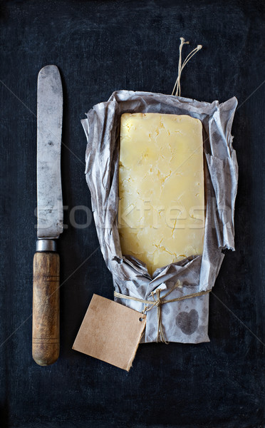 Mature cheddar cheese wrapped in rustic paper and a vintage knife. Stock photo © Photooiasson