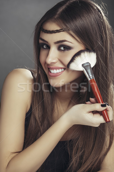Happy woman applying makeup on her face Stock photo © photosebia