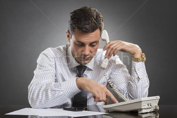Successful businessman dialing on phone Stock photo © photosebia
