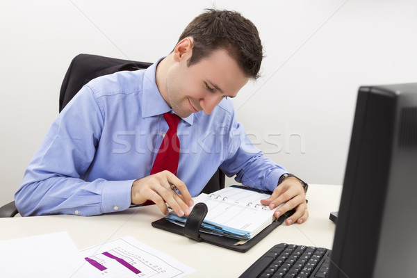 Happy entrepreneur consulting his agenda Stock photo © photosebia