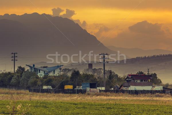 Coucher du soleil distant maisons montagnes Photo stock © photosebia