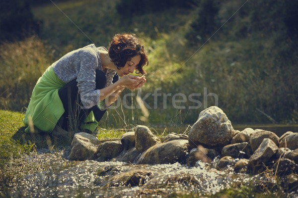 Woman drinking mountain stream water Stock photo © photosebia