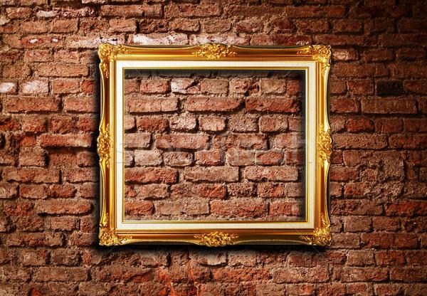 Golden frame against grunge brick wall Stock photo © photosoup