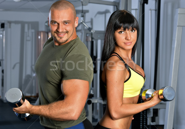Stock fotó: Man and woman are doing exercises in a sport club.