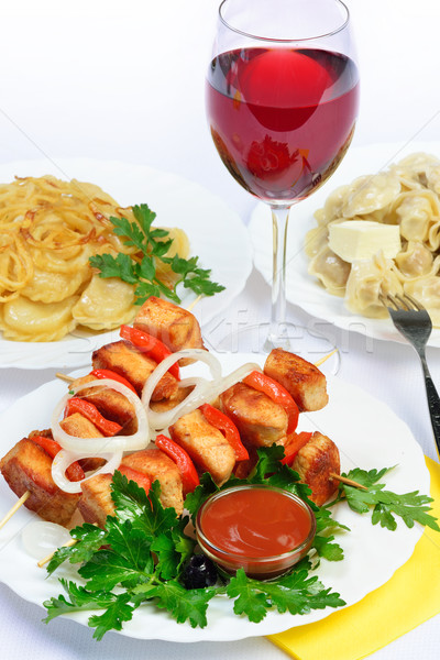 table with food of meat on skewer, dumplings and gass of red win Stock photo © Pilgrimego