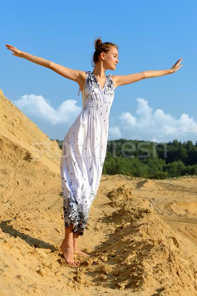 Gyönyörű nő pózol homok hely hosszú ruha Stock fotó © Pilgrimego