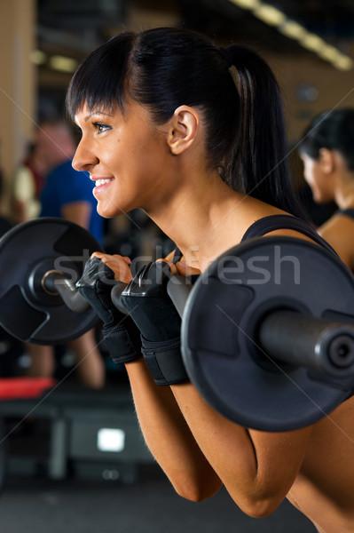 Beautiful woman is doing exercises with the bar Stock photo © Pilgrimego