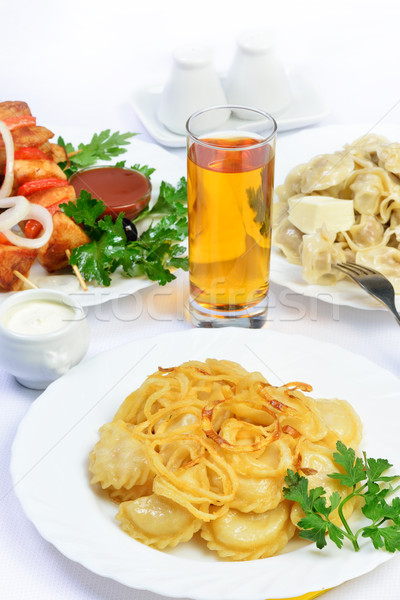 table with food of meat on skewer, dumplings and gass of juice. Stock photo © Pilgrimego
