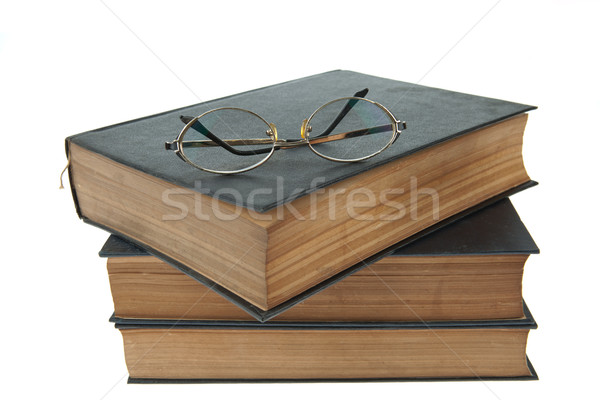 Stack Of Old Books With Eye Glasses Isolated On White