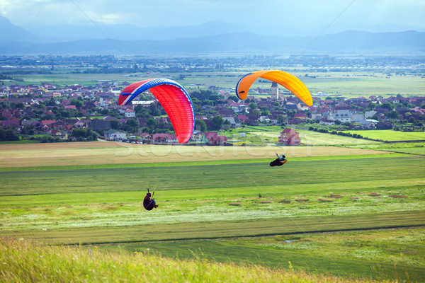 Paragliders flying over green fields Stock photo © pixachi