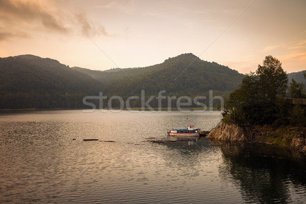 Small boat on the artificial lake behind the Bicaz Dam, at sunse Stock photo © pixachi